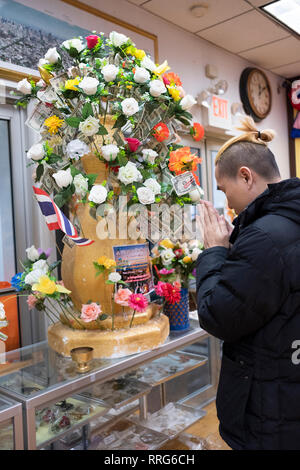 A devout Buddhist worshipper attaches a dollar bill to an orange artificial flower to donate to a temple in upstate New York. - Stock Image