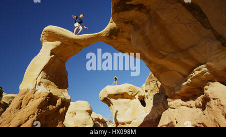 Low angle view of climbers balancing on scenic rock formations under clear blue sky - Stock Image