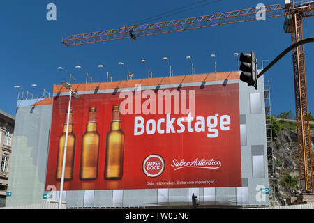 Outdoor advertising hoarding in Porto for the local beer SuperBock - Stock Image