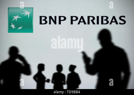The BNP Paribas logo is seen on an LED screen in the background while a silhouetted person uses a smartphone in the foreground (Editorial use only) - Stock Image