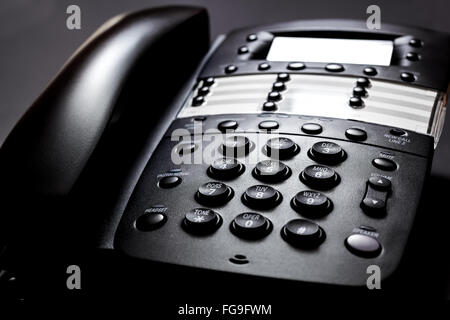 Business Telephone. Modern black landline telephone on a black background. - Stock Image