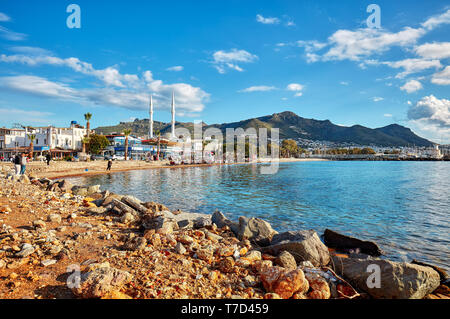 Bodrum, Turkey-January, 2019: Turgutreis bay and people relaxing on the seashore on a sunny winter afternoon in Bodrum, Mugla, Turkey. Editorial. - Stock Image