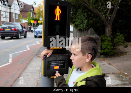A young boy waiting to cross the road at a pedestrian traffic lights crossing sign in an urban area UK  KATHY DEWITT - Stock Image