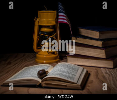 Stacked vintage books closed on a desk with an old yellow German lamp, a pipe and an american flage - classic litereracy concept - Stock Image