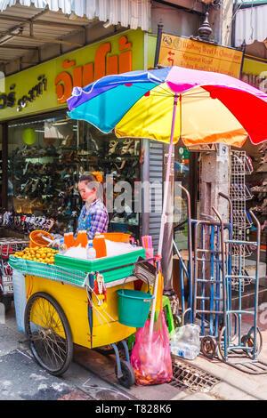 Bangkok, Thailand - April 21st 2011. Orange juice vendor under a colourful umbrella. Fruit juices are a popular drinl. - Stock Image