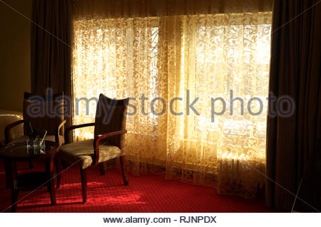 Hotel room interior, showing net curtains, chairs and small table. - Stock Image