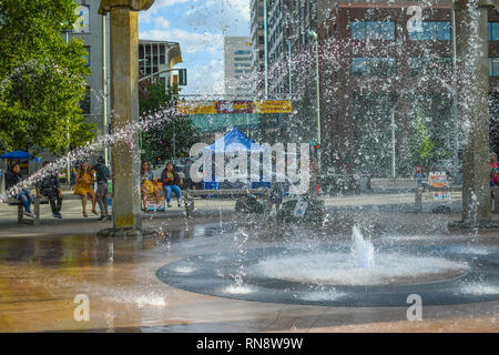 Tourists and locals enjoy a summer day at Riverfront Park in Spokane, Washington, as they sit around the Rotary Fountain and watch the water spray - Stock Image
