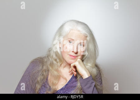 Headshot of a mature woman with beautiful curly long gray hair in front of white background, copy space. - Stock Image