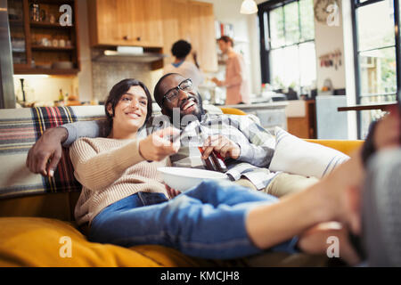 Smiling young couple watching TV, drinking beer and eating popcorn on living room sofa - Stock Image