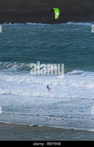 Kiteboarder kitesurfing in rough sea at Crantock Beach in Newquay in Cornwall. - Stock Image