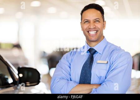 cheerful car salesman standing in showroom - Stock Image