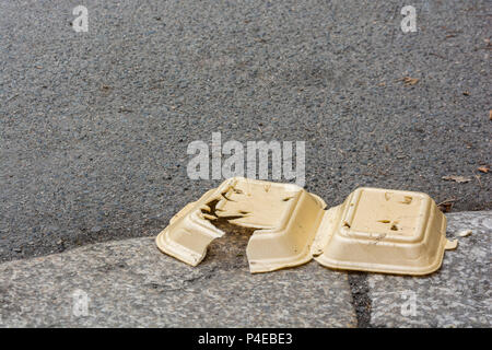 Discarded styrene takeaway box littering kerbside in Truro, Cornwall. Metaphor single-use plastics, plastic pollution UK, environmental pollution. - Stock Image