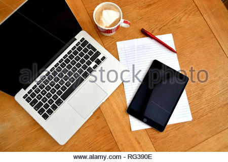 Flat lay style image with laptop computer, note paper and pen. Black phone / tablet used to help create lists. Coffee cup with coffee on wooden table. - Stock Image