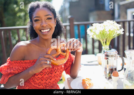 Portrait smiling, confident young woman with pretzel enjoying breakfast on sunny balcony - Stock Image