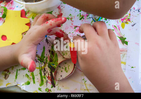 Child making a buttlerfly with recycled materials and EVA foam. Placing googly doll eyes - Stock Image