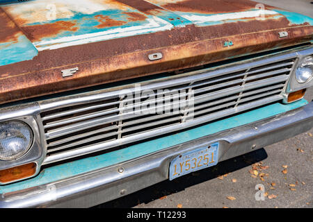 Front of old rusty turquoise Ford pickup truck with California license plate - Stock Image