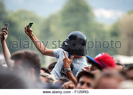 Selfie mania during concerts : young man wearing Darth Vader helmet (from Star Wars) taking self portrait - Stock Image