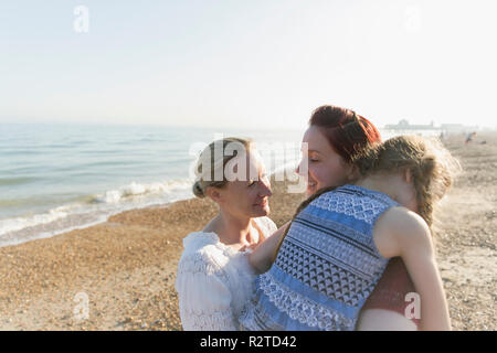 Lesbian couple hugging daughter on sunny beach - Stock Image