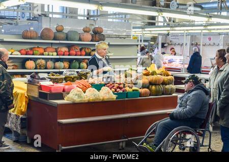 Man in wheelchair at the Market at the central station of Riga, Latvia (Jānis Sauka, Veikals) - Stock Image