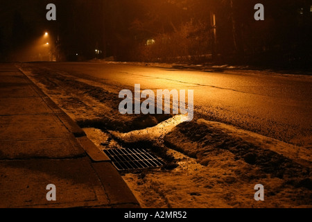 A dark and foggy night lit up by streetlamps in calgary - Stock Image