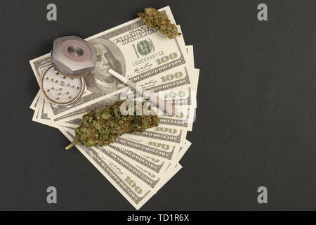 Closeup of grinder and dollar bill with benjamin franklin smokeing rolled joint isolated on black studio background - Stock Image