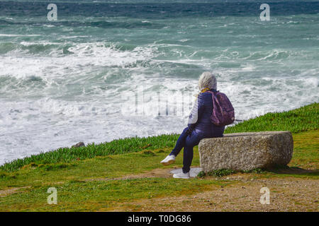 A woman watching the waves and sitting on a large rock on the Headland in Newquay in Cornwall. - Stock Image
