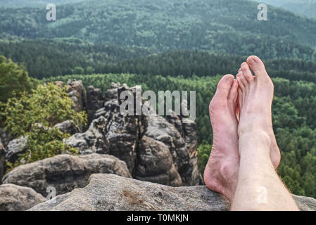 Tired hikers legs without shoes. Naked male hairy legs take a rest on peak of rock. - Stock Image