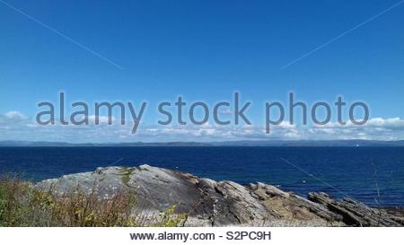 Deep blue sea, and blue sky. Taken from the Isle of Arran, Scotland. - Stock Image