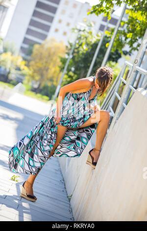 Young woman flashing legs heels - Stock Image
