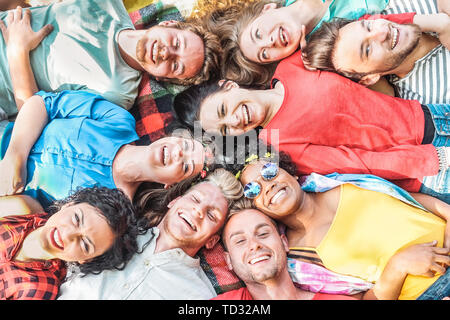 Group of diverse friends having fun outdoor - Happy young people lying on grass after picnic and laughing together - Stock Image