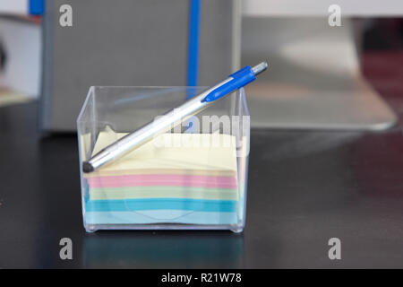 Stack of post it notes and a pen on a desk - Stock Image