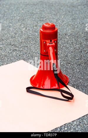 Red plastic modern megaphone bullhorn face down on ground and top of blank paper poster sign on outdoor pavement, with black strap. - Stock Image