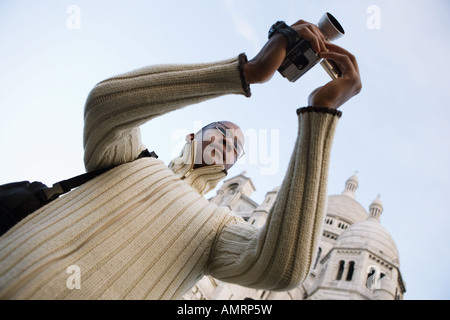 Low angle view of African man video recording - Stock Image