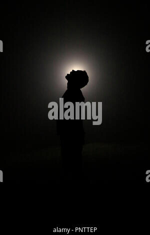 Silhouette in the Dark, Head Leaning Backwards with Open Mouth. Light behind Head. - Stock Image