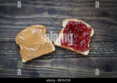 Top view of open face homemade peanut butter and strawberry Jelly sandwich on oat bread, over a rustic wooden background. - Stock Image