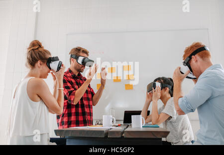 Business people using virtual reality goggles in meeting in office. Team of developers testing virtual reality headset. - Stock Image