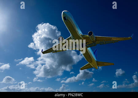 An artistic skyscape view of a commercial passenger jet aircraft flying in a vibrant blue sky, with bright white coloured Cumulonimbus clouds.Sydney - Stock Image