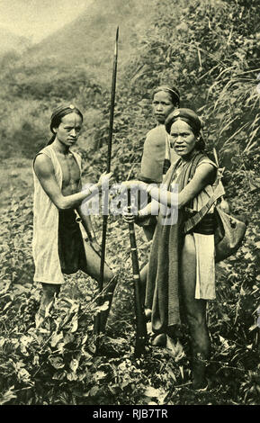 Three huntsmen of the Atayal (Tayal, Tayan) tribe, Formosa (now Taiwan). They were based around the mountainous region to the north of the island, which was at this time a Japanese province. Seen here with a long spear and a matchlock gun. - Stock Image