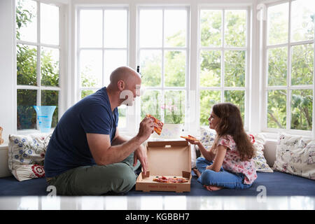 Dad and daughter sit on window seat at home sharing a pizza - Stock Image