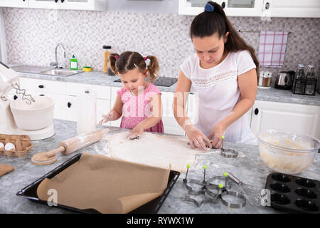 Happy Mother And Daughter Making Cookies With Molds At Kitchen - Stock Image