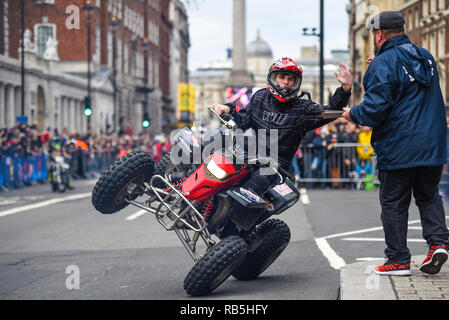 Moto Stunts International motorbike display team at London New Year's Day Parade. Quad bike stunt in Whitehall with Nelson's Column - Stock Image