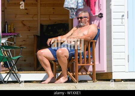 Lyme Regis, Dorset, UK.  4th July 2019. UK Weather.  A sunbather outside a seafront beach hut at the seaside resort of Lyme Regis in Dorset enjoying a day of clear skies and scorching hot sunshine.   Picture Credit: Graham Hunt/Alamy Live News - Stock Image