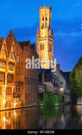 Famous view of Bruges tourist landmark attraction - Rozenhoedkaai canal with Belfry and old houses along canal with tree in the night. Belgium - Stock Image
