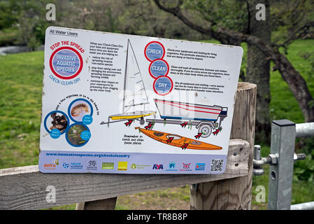 A sign telling outdoor water users to Check, Clean and Dry their boats and trailers to stop the spread of invasive aquatic species - Stock Image