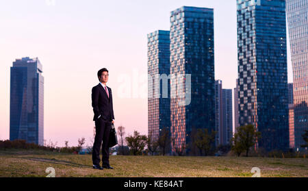 Businessman standing outdoors at sunset - Stock Image