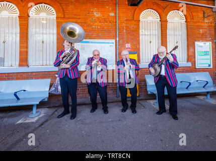 Elderly musicians from the Belmond Venice Simplon Orient Express in striped blazers perform on the platform at Folkestone West railway station, Kent - Stock Image