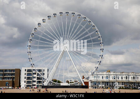 WORTHING, UK - JULY 13, 2019: People enjoy a day out on the pebble beach in Worthing with newly opened Wheel - Stock Image
