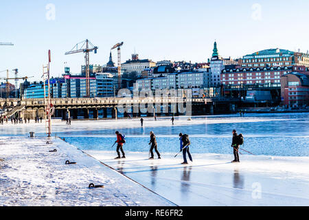 Ice skaters on Riddarfjarden, Lake Malaren, with the island of Sodermalm in the background and cranes working on the new underground station at Slussen. Stockholm, Sweden. 20th January, 2019. - Stock Image