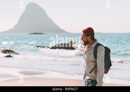 Man traveler relaxing on ocean beach enjoying landscape summer traveling lifestyle adventure vacations in Norway active trip exploring outdoor - Stock Image