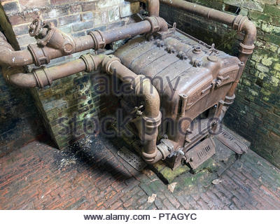 Large old coal fired cast iron 'Robin Hood Beeston' boiler, greenhouse heater, Calke Abbey, Ticknall, Derbyshire, England, UK - Stock Image